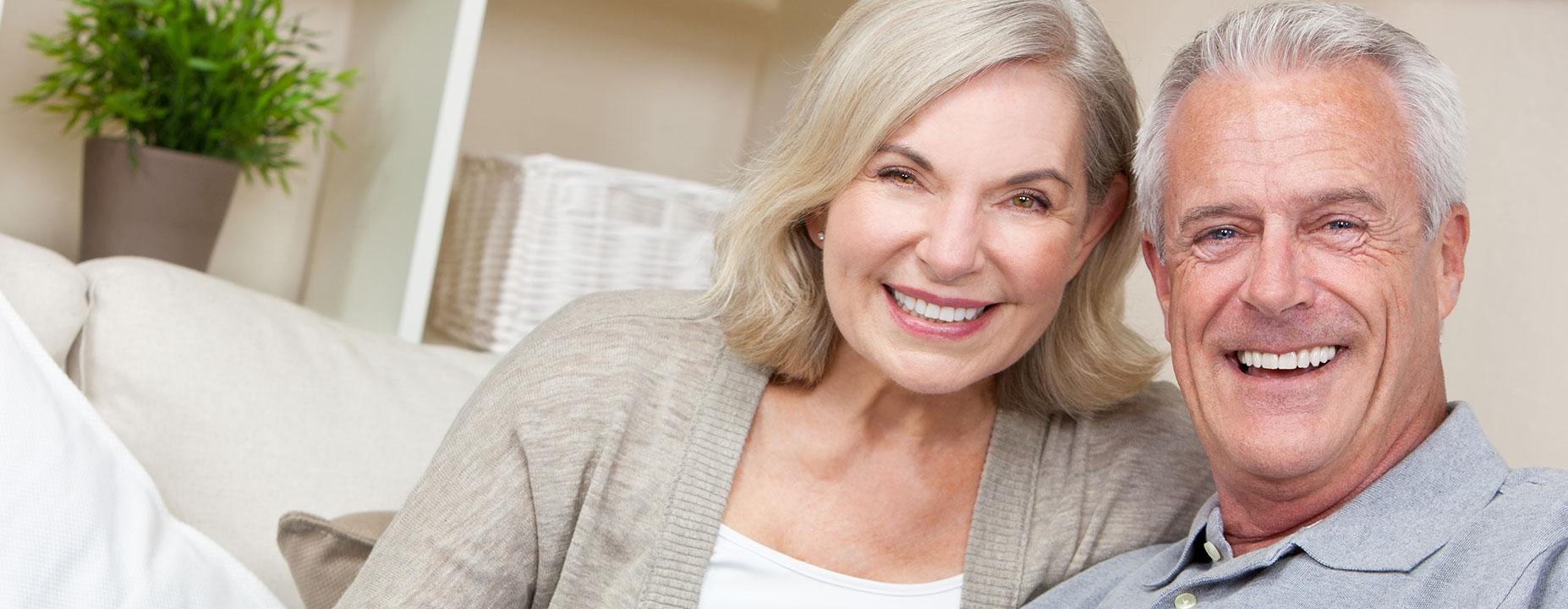 Middle age couple smiling after having restorative dental services