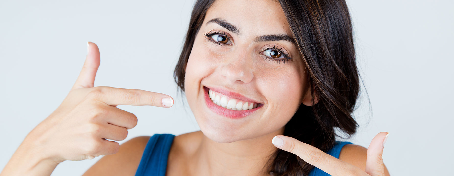 Young lady showing her teeth after doing teeth whitening