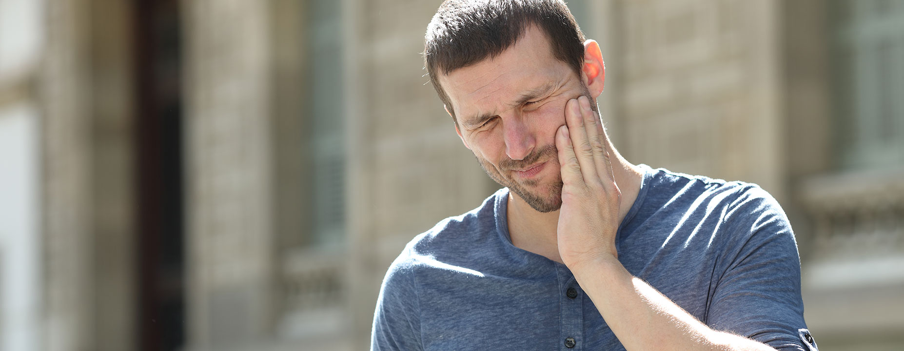 Man suffering toothache in the street